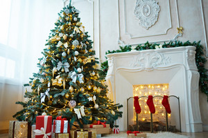 Decorated xmas tree, packages with gifts and red socks on fireplace in the room