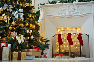 Decorated xmas tree, stack of gift-boxes and fireplace with red socks prepared for Christmas night
