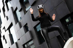Dedicated Woman Wearing Virtual Reality Technology Glasses Against Building