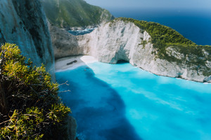 Defocused Navagio beach with green vegetation in foreground. Famous landscape of Zakinthos island, Greece, retro vintage toned
