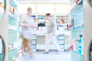 Defocused picture of customers shopping in pharmacy