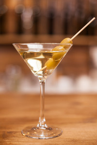 Delicious martini drink with green olives on stick over a wooden bar counter. Fresh drink. Celebration drink.