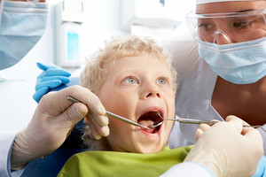 Dental inspection is being given to little boy surrounded by dentist and his assistant