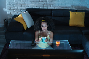 Depressed African American girl alone at home during movie night. Young black woman crying while watching a drama show.