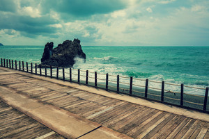 Deserted beach in stormy weather. Wooden embankment