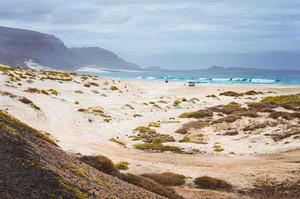 Deserted beach of Praia Grande. Spectacular sand dunes, ocean waves and black volcanic mountains behind. North of Calhau, Sao Vicente Island Cape Verde