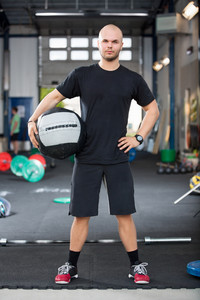 Determined Male Athlete Holding Medicine Ball In Health Club