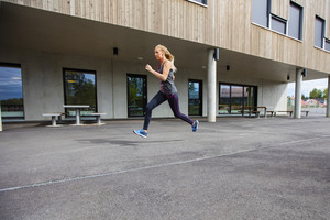 Determined Young Woman Running By Building