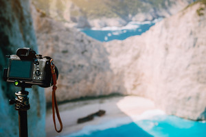 Digital camera on tripod capture photo of Shipwreck in Navagio beach in morning sun light. Famous visiting landmark location on Zakynthos island, Greece