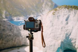 Digital photo camera on tripod against huge cliff rocks of Navagio beach in morning sun light. Famous visiting landmark location on Zakynthos island, Greece