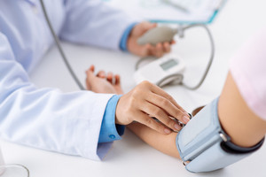 Doctor taking pulse of the patient who has life insurance policy, view from the top