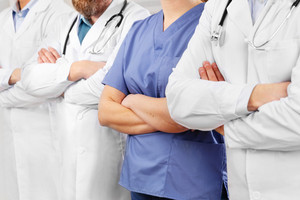 Doctors and nurses in healthcare team with arms crossed in a row in hospital