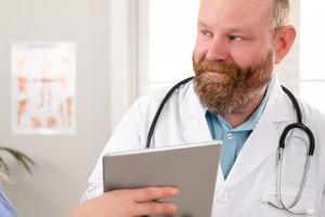 Doctors discussing report about a patient at tablet computer in hospital