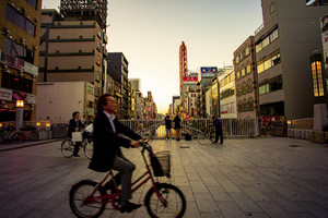 dotonbori osaka japan - november6,2018 unidentified man riding bicycle passing dotonbori bridge ,dotonbori is one of most pupular shopping destination in heart of osaka japan