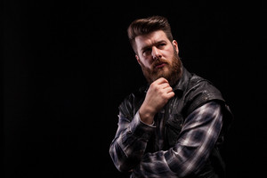 Dramatic portrait of beard man wearing a leather vest over black background. Stylish man. Good hair style