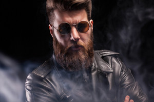 Dramatic studio light on handsome bearded man with sunglasses over black background. Handsome man. Attractive man.