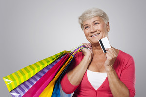 Dreaming senior woman with shopping bags and credit card