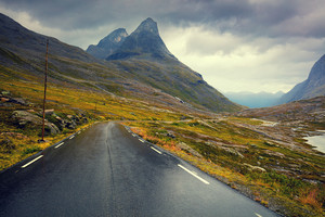 Driving a car on mountain road. Road among mountains with dramatic stormy cloudy sky landscape. Beautiful nature in Norway.