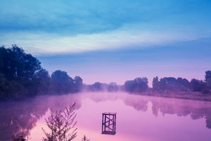 Early in the morning, dawn over the lake. Calm lake before sunrise. A misty morning, a rural landscape, a desert, a mystical feeling