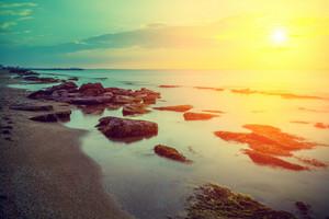 Early morning, sunrise over the sea. Rocky sea shore