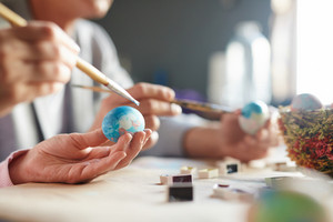 Easter egg and paintbrush in human hands