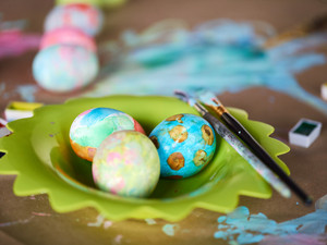 Easter eggs and paintbrushes on plate