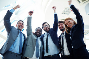 Ecstatic business partners in suits raising their arms and expressing triumph