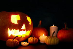 Eerie jack-o-lantern, burning candles and pumpkins in darkness