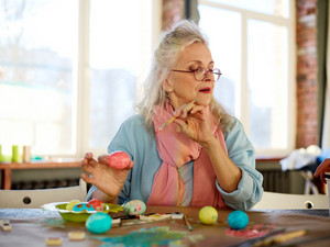 Elderly woman painting Easter eggs before holiday