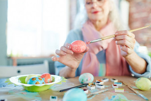 Elderly woman with paintbrush preparing eggs for Easter