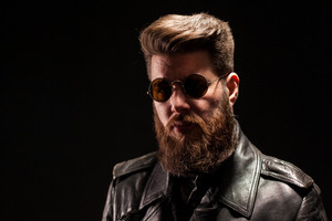 Elegant bearded man with leather jacket and sunglasses over black background. Rocker man. Attractive man.