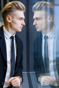 Elegant businessman and his reflection in window