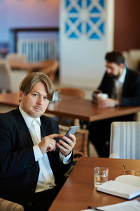 Elegant businessman sitting in cafe and writing sms