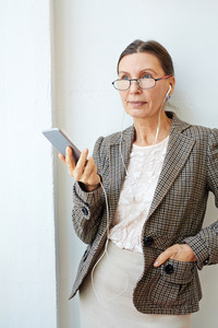 Elegant mature female with earphones listening to music