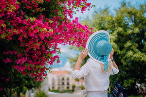 Elegant traveler woman with straw hat smelling beautiful colorful flowers on the islands of Greece during summer time. Romantic Traveling vacation concept