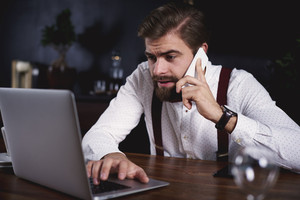 Embarrassed businessman working with technology