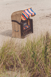 Empty multicolord roofed chair on sandy beach in Travemunde, North Germany. Dune with dry grass in foreground