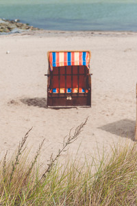 Empty red roofed chair on sandy beach in Travemunde, North Germany. Dry grass in foreground