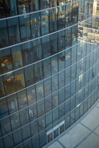 Entrance of modern glass office building and empty pavement in front of it, high angle view