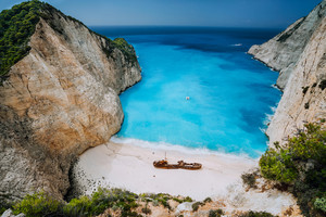 Epic view of Shipwreck middle of sandy Navagio beach surrounded by azure deep turquoise sea saltwater and huge white cliff limestone rocks. Zakynthos island, Greece