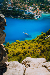 Epic view to blue bay of Assos village Kefalonia from Fortress above. White yacht at anchor in calm beautiful colored lagoon water surrounded by pine and cypress trees. Greece