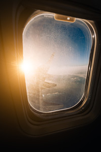 Evening airplane flight in twilight sky. Sunset view in cabin frozen window frame