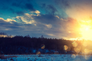 Evening snowy landscape at sunset with sun rays