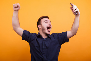 Excited young man raising up his arms on yellow background