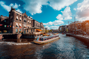 Excursion boat on the river Amstel. Cityscape of Amsterdam Netherlands. Amazing cloudscape on sunny autumn day. Vacation weekend in Europe