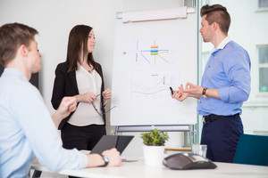 Executive Explaining Chart To Coworkers In Office