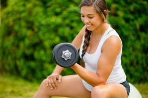 Expectant Female Exercising With Dumbbells To Strengthen Arms In