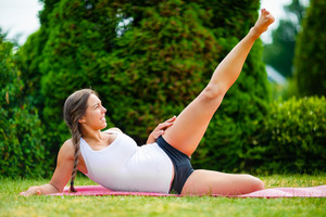 Expectant Woman Doing Side Reclining Leg Lift In Park