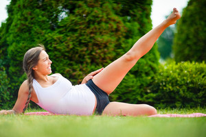 Expectant Woman Performing Side Reclining Leg Lift On Yoga Mat