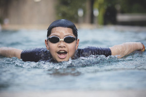 face of asian boy swimming in water sport pool
